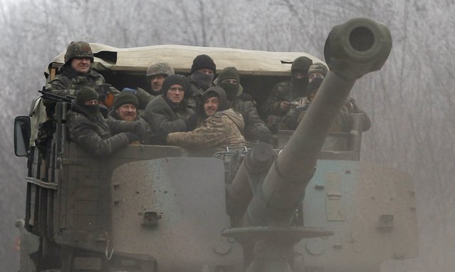 Ukrainian government soldiers ride on a vehicle on the road between the towns of Dabeltseve and Artemivsk, Ukraine, Saturday, February 14, 2015. (Photo by Petr David Josek/AP Photo)