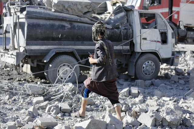 A man walks past a damaged water tanker truck at the site of a Saudi-led air strike in Yemen's capital Sanaa January 4, 2016. (Photo by Khaled Abdullah/Reuters)