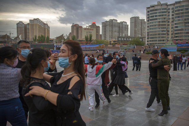 People dance to music at a public square in Aksu in western China's Xinjiang Uyghur Autonomous Region, as seen during a government organized trip for foreign journalists, Tuesday, April 20, 2021. (Photo by Mark Schiefelbein/AP Photo)