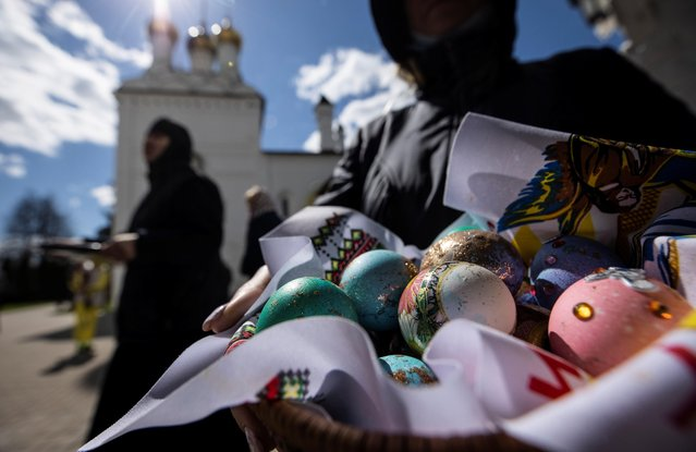 A woman shows her painted eggs on the eve of Orthodox Easter in the Joseph-Volokolamsk monastery in Moscow region, Russia on May 1, 2021. (Photo by Maxim Shemetov/Reuters)