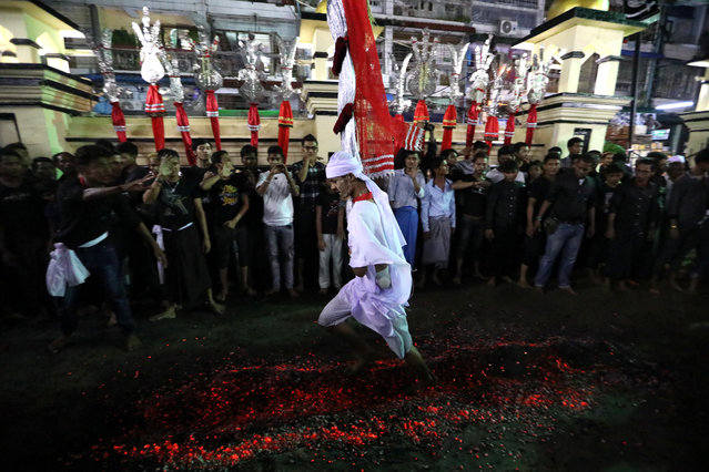 A Shi'ite Muslim walks on hot coals at a ceremony during the Ashura festival at a mosque in central Yangon, Myanmar on September 18, 2018. (Photo by Ann Wang/Reuters)