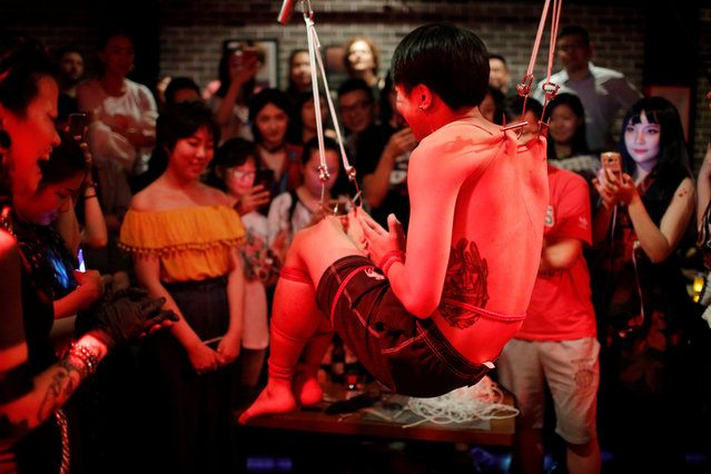 Spectators watch as Viktor Liu is suspended from hooks pierced through his skin by professional body artist Wei Yilaien at a bar in Shanghai, China on September 16, 2018. (Photo by Aly Song/Reuters)