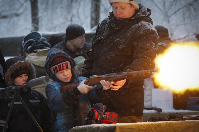 A military instructor helps a boy to shoot a rifle with blanks at a weapon exhibition during a military show in St.Petersburg, Russia, Sunday, January 17, 2016. (Photo by Dmitry Lovetsky/AP Photo)