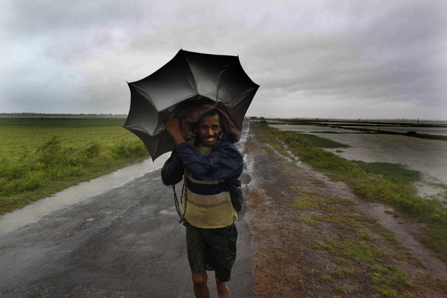 An Indian villager braving strong winds and rain walk to a safer place, in village Podampeta, in Ganjam district about 200 kilometers  (125 miles) from the eastern Indian city Bhubaneswar, India, Saturday, October 12, 2013. Strong winds and heavy rains pounded India's eastern coastline Saturday, as hundreds of thousands of people took shelter from a massive, powerful Cyclone Phailin expected to reach land in a few hours. (Photo by Biswaranjan Rout/AP Photo)