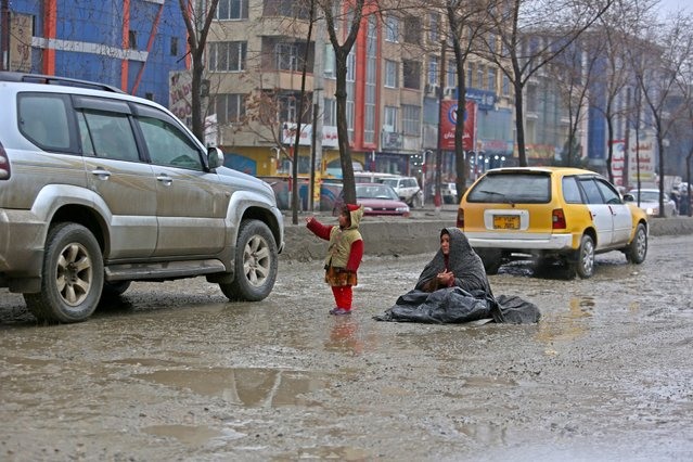 An Afghan girl begs for money as her mother sits in the middle of the road during a rainy day on the outskirts of Kabul, Afghanistan, Friday, March. 6, 2015. (AP Photo/Rahmat Gul)