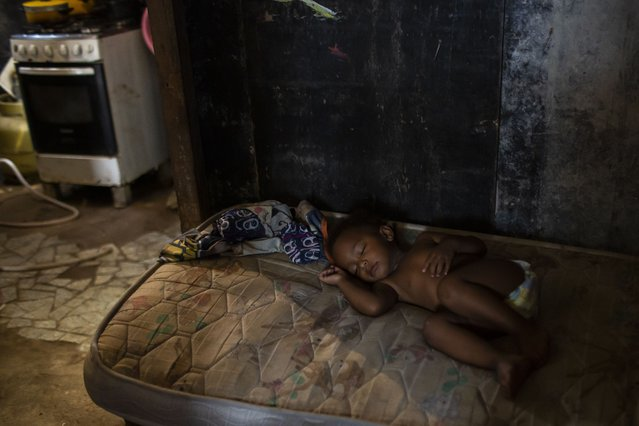 Ana Beatriz sleeps on a mattress while her mother Debora Estanislau, who before the new coronavirus pandemic hit made a living as a domestic worker cooks, in the house where she lives with her four children at the Cidade de Deus favela, in Rio de Janeiro, Brazil, Sunday, April 18, 2021. (Photo by Bruna Prado/AP Photo)