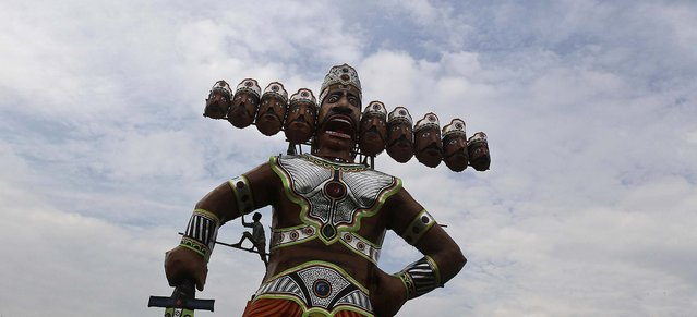 Bubul Haque, an Indian artist, prepares an effigy of the demon king Ravana as part of Dussehra festival celebrations, in Gauhati, India, on Oktober 13, 2013. The festival commemorates the victory of Hindu god Rama over demon king Ravana, and is a celebration of the victory of good over evil. (Photo by Anupam Nath/Associated Press)