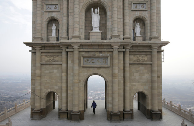 A villager walks through a Catholic church's building to pray, on the top of a hill, near a Catholic church on the outskirts of Taiyuan, North China's Shanxi province, December 24, 2016. (Photo by Jason Lee/Reuters)