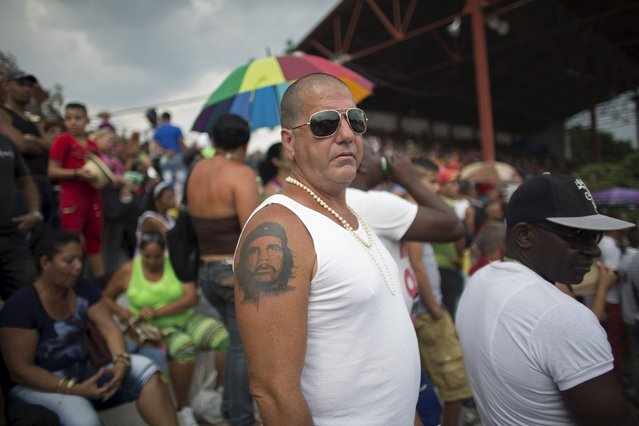 """A man with a tattoo of Cuba's revolutionary hero Ernesto """"Che"""" Guevara watches a rodeo show at the International Livestock Fair in Havana March 22, 2015. (Photo by Alexandre Meneghini/Reuters)"""
