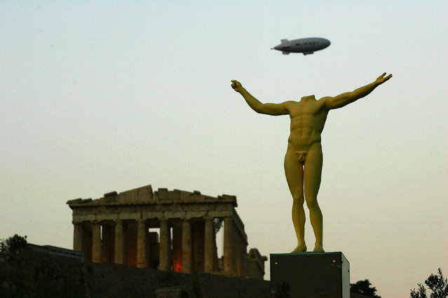 A zeppelin flies over the Parthenon on the eve of Athens 2004 Olympic Games during the festivities for the Athens 2004 Summer Olympic Games Opening Ceremony on August 13, 2004 in Athens, Greece. (Photo by Daniel Berehulak/Getty Images)