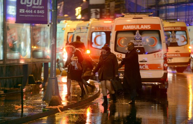 People flee as ambulances are on the attack site on January 1, 2017 in Istanbul. .At least two people were killed in an armed attack Saturday on an Istanbul nightclub where people were celebrating the New Year, Turkish television reports said. (Photo by AFP Photo/Ihlas News Agency)