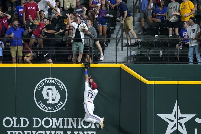 Texas Rangers right fielder Joey Gallon (13) leaps to the top of the fence and watches a fan reache up to attempt catching a three-run home run ball hit by Detroit Tigers' Eric Haase in the seventh inning of a baseball game in Arlington, Texas, Tuesday, July 6, 2021. (Photo by Tony Gutierrez/AP Photo)