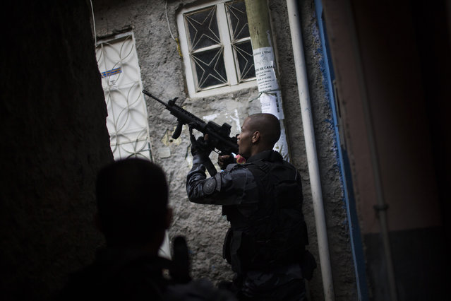 Military police officers patrol an alley at the Roquette Pinto shantytown, part of the Mare slum complex in Rio de Janeiro, Brazil, Wednesday, April 1, 2015. (Photo by Felipe Dana/AP Photo)