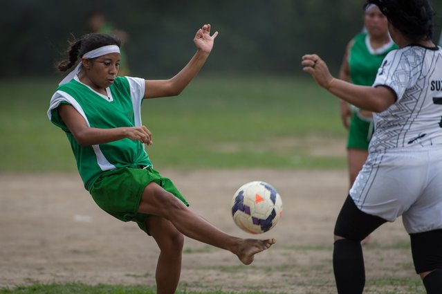 Female indigenous players vie for the ball during the final match of Peladao, the amateur football tournament, in Manaus, Amazonas state, Brazil, on November 24, 2013. (Photo by Yasuyoshi Chiba/AFP Photo)
