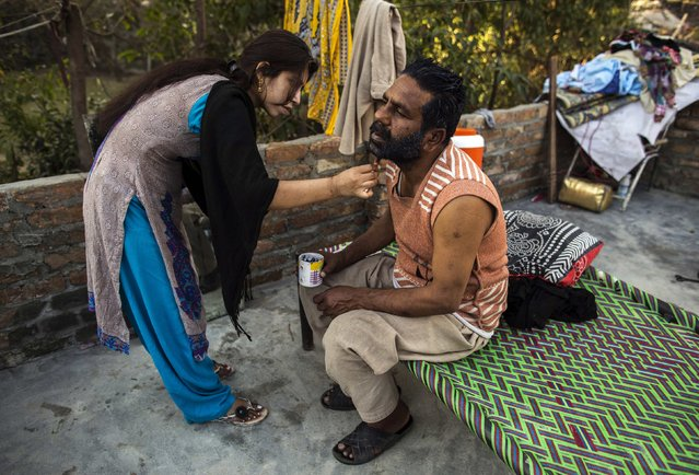 A woman dyes her husband's beard at a slum in Islamabad March 12, 2015. (Photo by Zohra Bensemra/Reuters)