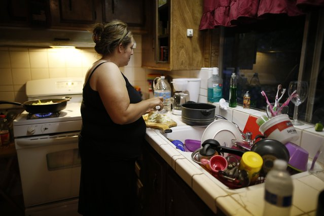 Angelica Gallegos, 37, whose well has run dry, chops vegetables as she stands next to her sink where she washes dishes with bottled water in Porterville, October 14, 2014. (Photo by Lucy Nicholson/Reuters)