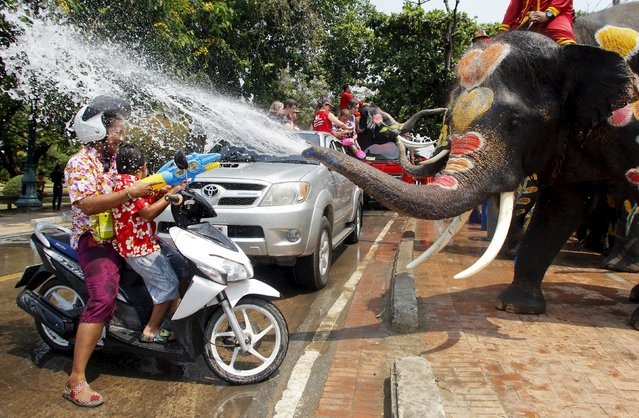 Elephants spray villagers with water in celebration of the Songkran water festival in Thailand's Ayutthaya province, north of Bangkok, April 10, 2015. (Photo by Chaiwat Subprasom/Reuters)