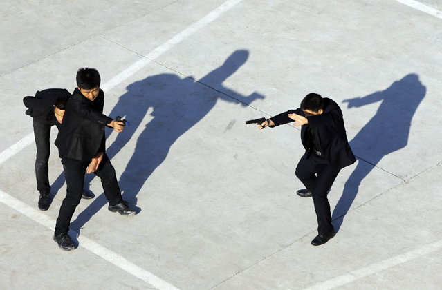 Trainees point replica pistols as they take part in a training session at the Tianjiao Special Guard/Security Consultant training camp on the outskirts of Beijing, December 11, 2013. (Photo by Jason Lee/Reuters)