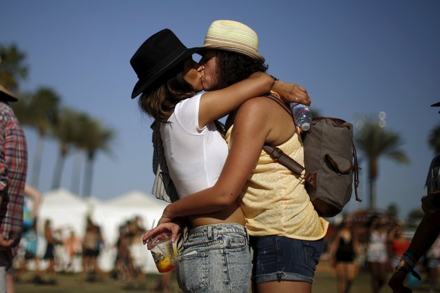 A couple kisses as they wait in line for food at the Coachella Valley Music and Arts Festival in Indio, California April 11, 2015. (Photo by Lucy Nicholson/Reuters)