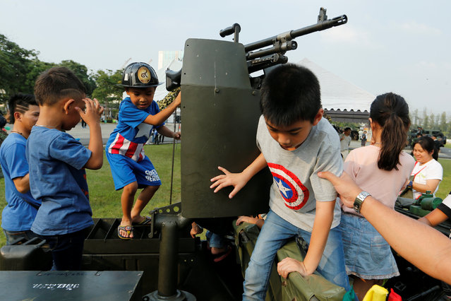 Children play with a weapon on top of an army vehicle during Children's Day celebration at a military facility in Bangkok, Thailand January 14, 2017. (Photo by Jorge Silva/Reuters)