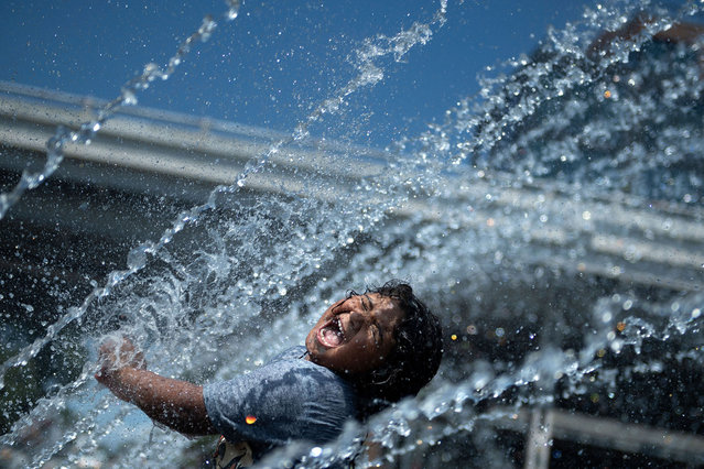 Micaela Montelara plays in the fountain at Georgetown Waterfront Park during a heatwave on August 13, 2021, in Washington, DC. July was the hottest month ever recorded, according to data released, by the National Oceanic and Atmospheric Administration (NOAA)  on August 13, 2021. The combined land- and ocean-surface temperature around the world, according to NOAA, was 1.67 degrees Fahrenheit (0.93°C) above the 20th century average of 60.4F (15.7°C) since record-keeping started 142 years ago. (Photo by Brendan Smialowski/AFP Photo)