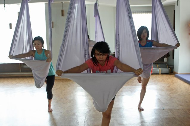 Some women climb up to the hammocks during the Anti-Gravity yoga class at Svarga e-Motion Sanctuary at Dharmawangsa Square, Jakarta, Saturday, April 18, 2015. (Photo by Jurnasyanto Sukarno/JG Photo)