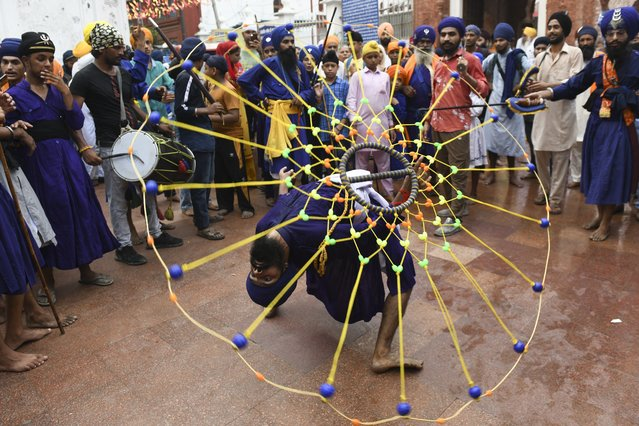 """A Sikh youth performs the Sikh martial art known as """"Gatka"""" on the occasion of the 417th anniversary of the installation of the Guru Granth Sahib, at the Golden Temple in Amritsar on September 7, 2021. (Photo by Narinder Nanu/AFP Photo)"""