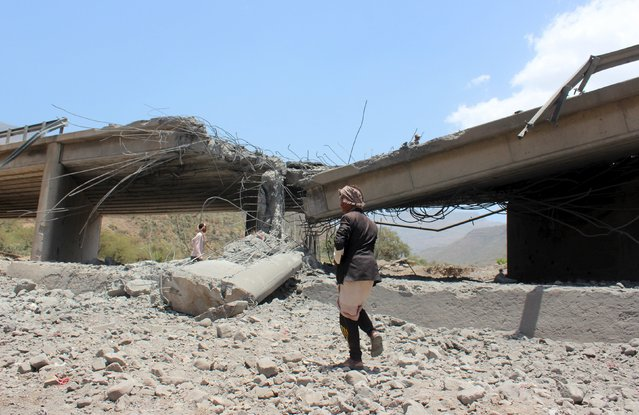 A man walks past a bridge after it was hit by an air strike in Yemen's central province of Ibb April 21, 2015. (Photo by Reuters/Stringer)