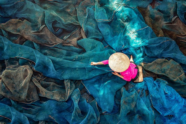 A worker repairs fishing nets, which can stretch to more than 20 metres in length, in Sakon Nakhon, Thailand on August 12, 2021. (Photo by Chanwit Wanset/Solent New)