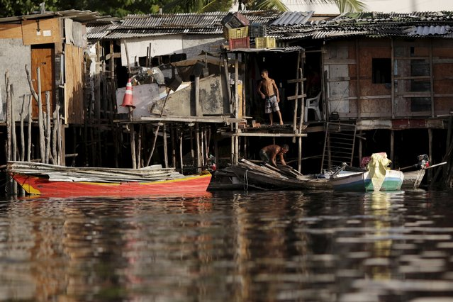 "A men are seen in front of her stilt house a lake dwelling also known as palafitte or ""Palafito"" in Recife, Brazil, March 1, 2016. (Photo by Ueslei Marcelino/Reuters)"