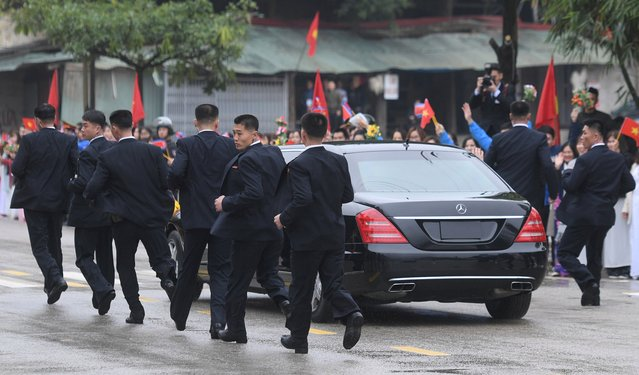 North Korean bodyguards run along a limousine transporting Kim Jong Un upon his arrival in Dong Dang, Vietnam, February 26, 2019. The second meeting of the US President and the North Korean leader, running from 27 to 28 February 2019, focuses on furthering steps towards achieving peace and complete denuclearization of the Korean peninsula. (Photo by Reuters/Stringer)