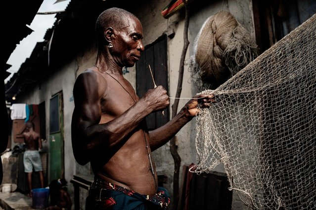 A fisherman who moved from Ogoniland repairs a fishing net in front of his house at Egede informal settlement in Port Harcourt, southern Nigeria, on February 21, 2019. (Photo by Yasuyoshi Chiba/AFP Photo)