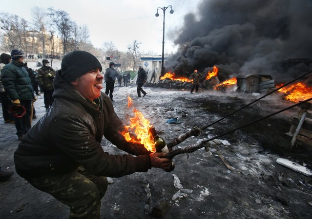 Protesters use a large slingshot to hurl a Molotov cocktail at police in central Kiev, Ukraine, Thursday January 23, 2014. Thick black smoke from burning tires engulfed parts of downtown Kiev as an ultimatum issued by the opposition to the president to call early election or face street rage was set to expire with no sign of a compromise on Thursday. (Photo by Sergei Grits/AP Photo)