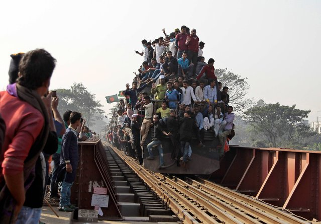 Bangladeshi Muslim devotees head to their homes in an over-crowded train after attending three-day Islamic Congregation on the banks of the River Turag in Tongi, 20 kilometers (13 miles) north of the capital Dhaka, Bangladesh, Sunday, January 26, 2014. Hundreds of thousands of Muslims attended the annual three-day event that is one of the world's largest religious gatherings being held since 1960's to revive Islamic tenets. It shuns politics and calls for peace. (Photo by A. M. Ahad/AP Photo)