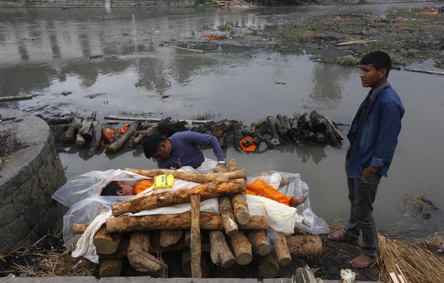 Suresh, 16, right, watches as a priest prepares the funeral pyre for his younger brother Umesh, 13, killed in Saturday's earthquake, at the Pashupatinath temple, on the banks of the Bagmati river, in Kathmandu, Nepal, Monday, April 27, 2015. (Photo by Manish Swarup/AP Photo)