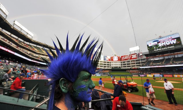 A rainbow arcs over Matt Stixrud's mohawk as ground crews prepare a wet field before the start of the first inning of a baseball game between the Texas Rangers and Seattle Mariners, Monday, April 27, 2015, in Arlington, Texas. (Photo by Brandon Wade/AP Photo)