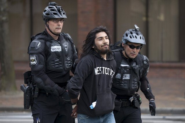 Police detain a demonstrator during an anti-capitalist protest in Seattle, Washington, May 1, 2015. (Photo by David Ryder/Reuters)