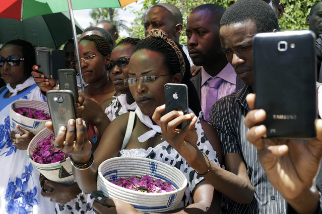 Friends and relatives of Jean Claude Niyonzima, who was killed during clashes with police over the move by President Pierre Nkurunziza to seek a third term in office, take pictures during his burial ceremony outside Bujumbura, Burundi, Saturday May 2, 2015. Many people have gathered in the streets over the past few days to protest against President Pierre Nkurunziza's decision to run for election as president for a third term in office. (Photo by Jerome Delay/AP Photo)