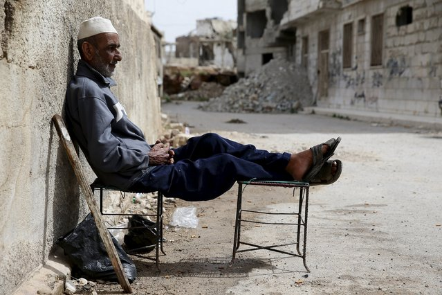 Khaled Kassmou, 70, sits along a street in the rebel held Qaboun neighborhood of Damascus, Syria March 13, 2016. (Photo by Bassam Khabieh/Reuters)