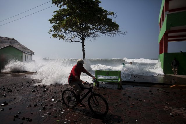 A man rides his bicycle as a wave crashes at La Libertad malecon on May 13, 2015. (Photo by Jose Cabezas/Reuters)