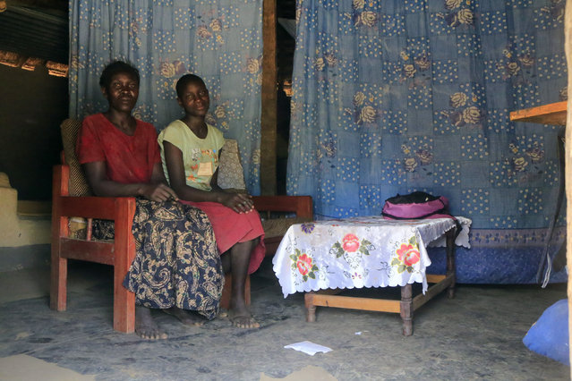 Lucy Oyela, 42, poses for a photograph with her daughter Abber Lillian, 14, at their home in Onang near Gulu town in northern Uganda February 16, 2014. Lucy is a farmer who finished her education at age 18. She said that when she was a child, she wanted to become a teacher when she grew up. Lucy says that she really wants for her daughter to become a nurse. Her daughter Abber Lillian says she doesn't know at what age she will finish education. (Photo by James Akena/Reuters)