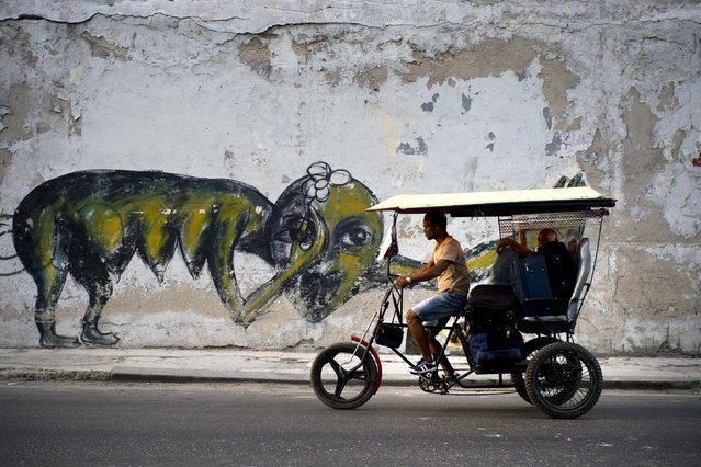 In this February 12, 2017 photo, the work of urban artist Yulier P. adorns a wall on a street in Havana, Cuba. Cuba has long had a thriving art scene and there has in recent years been a boom for works by some of the island's most famous painters. But the 27-year-old artist, whose full name is Yulier Rodríguez Pérez did not emerge from the artistic establishment and the kind of urban art he practices is unusual here. (Photo by Ramon Espinosa/AP Photo)