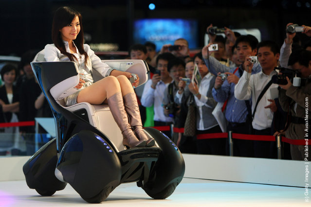 A model drives a Toyota i-REAL concept car