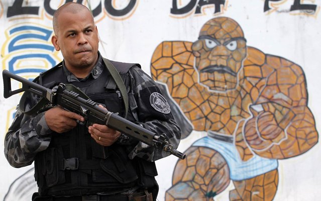 Police battalion patrol the area of Vila Kennedy, in the West Zone of Rio, during the police action, on March 12, 2014. (Photo by Marcos de Paula/Estadão Conteúdo)