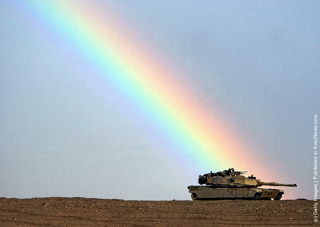 A rainbow breaks over the position of an M1/A1 Abrams tank