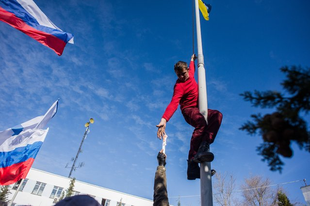 A member of a Pro-Russian self-defense force reaches for a knife, as he takes down a Ukrainian Navy flag at the Ukrainian Navy headquarters in Sevastopol, Crimea, Wednesday, March 19, 2014. (Photo by Andrew Lubimov/AP Photo)