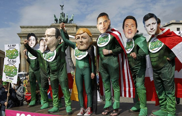 AVAAZ environmental activists wear masks depicting leaders of the countries members of the G7, (L-R) Japanese Prime Minister Shinzo Abe, British Prime Minister David Cameron, French President Francois Hollande, German Chancellor Angela Merkel, U.S. President Barack Obama, Italian Prime Minister Matteo Renzi and Canadian Prime Minister Stephen Harpe during a rally in front of the Brandenburg Gate near the venue where the Petersberg Climate Dialogue takes place in Berlin, Germany, May 19, 2015. (Photo by Fabrizio Bensch/Reuters)