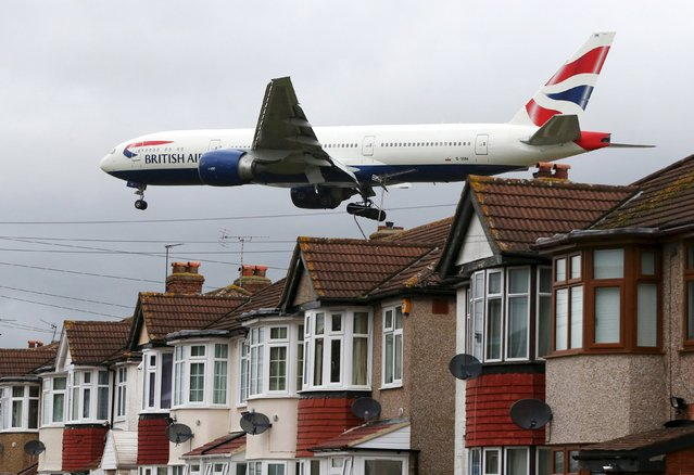An aircraft passes over houses at it lands at Heathrow Airport near London, Britain, December 11, 2015. Picture taken December 11, 2015. (Photo by Neil Hall/Reuters)
