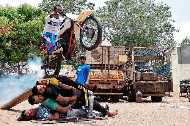 An Indian man, Kalpesh Modi, performs stunts with his motorcycle during the rehearsal for the forthcoming Lord Jagannath Rath Yatra, an annual Hindi festival, in Ahmedabad on June 23, 2019. The 142nd Lord Jagannath Rath Yatra festival in Ahmedabad is scheduled for July 4. (Photo by Sam Panthaky/AFP Photo)