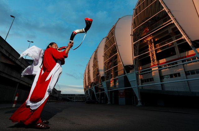 Peru soccer fan David Chauca blows on a horn outside the Beira Rio stadium during a practice session by Peru's national soccer team in Porto Alegre, Brazil, Monday, July 1, 2019. Peru will face Chile on July 3 in the semifinals for the Copa America. (Photo by Diego Vara/Reuters)